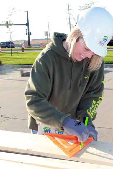 VisionBank Team Member Kim Purcell measures for a perfect panel build during our 5th Habitat for Humanity event.